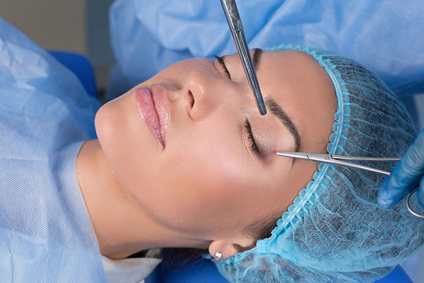 A female patient in the exam room for a brow lift